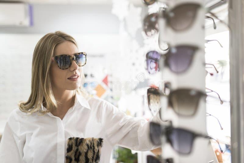 Schönheitsfrau im optischen Speicher mit der Sonnenbrille, die Anzeige betrachtet stockfotografie