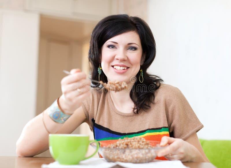 Schönheitsfrau isst Buchweizengetreide stockfoto