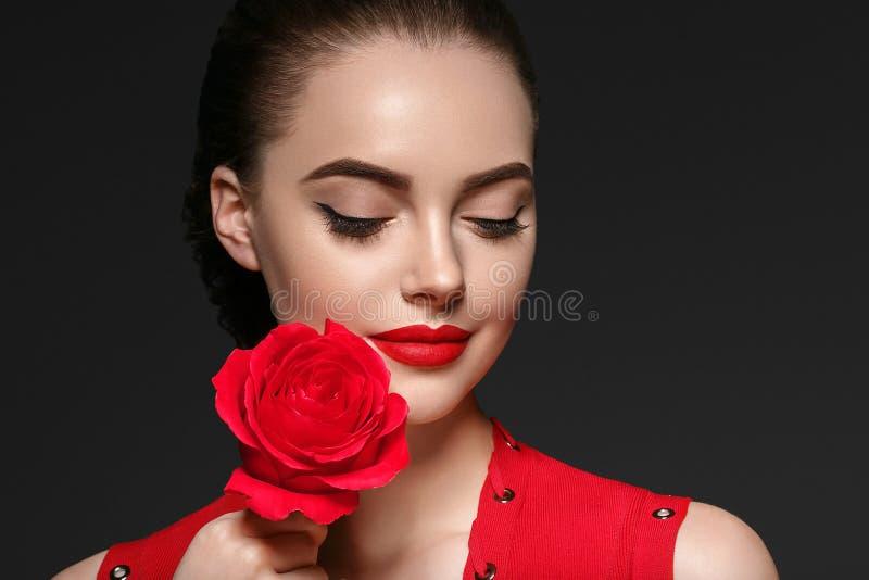 Schönheitsfrau mit dem schönen gelockten Haar und den Lippen der rosafarbenen Blume lizenzfreies stockfoto
