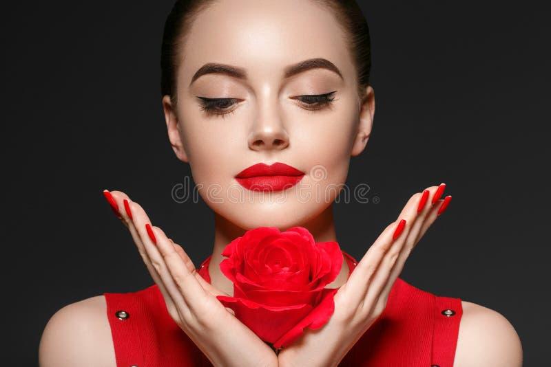 Schönheitsfrau mit dem schönen gelockten Haar und den Lippen der rosafarbenen Blume lizenzfreies stockbild
