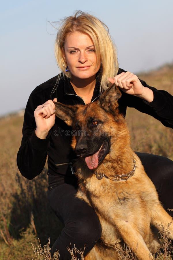 Schönheitsfrau und -schäferhund stockfoto