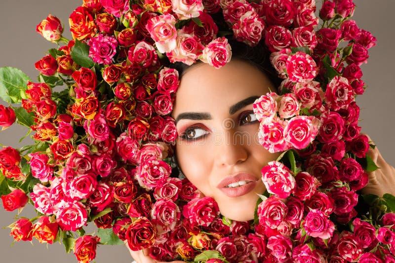 Schönheitsfrauen-Make-upgesicht mit roten Rosen blühen Kranz auf Kopf stockfoto