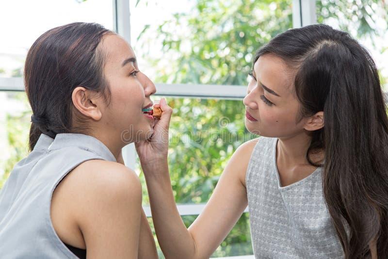 Schönheitsfrauen-Nehmenlippenstift, Freundinnen, die beim Make-up helfen Freundinnen, die herum mit Make-up täuschen Lächelndes Z lizenzfreie stockfotografie