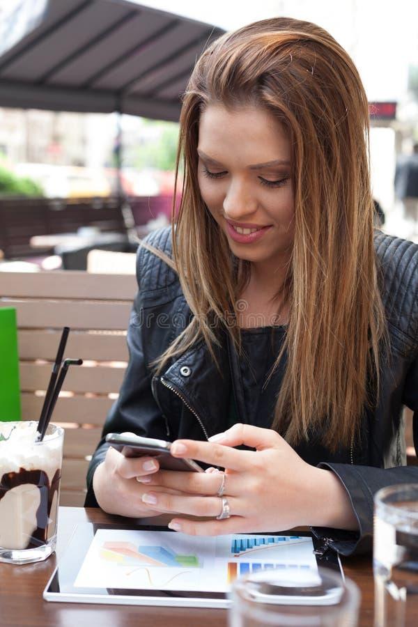 Schönheitsfrauen-Schreibensmitteilung am Handy in einem Straße caffe stockbild