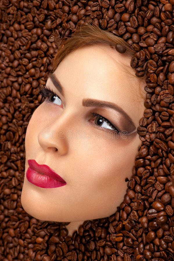 Schönheitsgesicht in den Kaffeebohnen lizenzfreie stockfotos