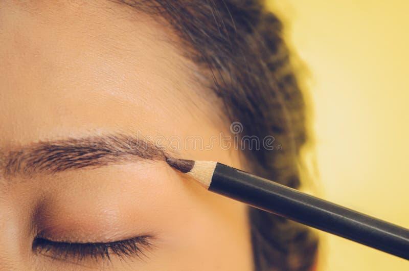 Schönheitsgesicht der Asiatin durch das Anwenden des Augenbrauenstifts und der glatten Haut durch Kosmetik stockfotos