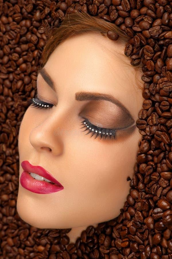 Schönheitsgesicht mit hellem Make-up in den Kaffeebohnen lizenzfreie stockbilder