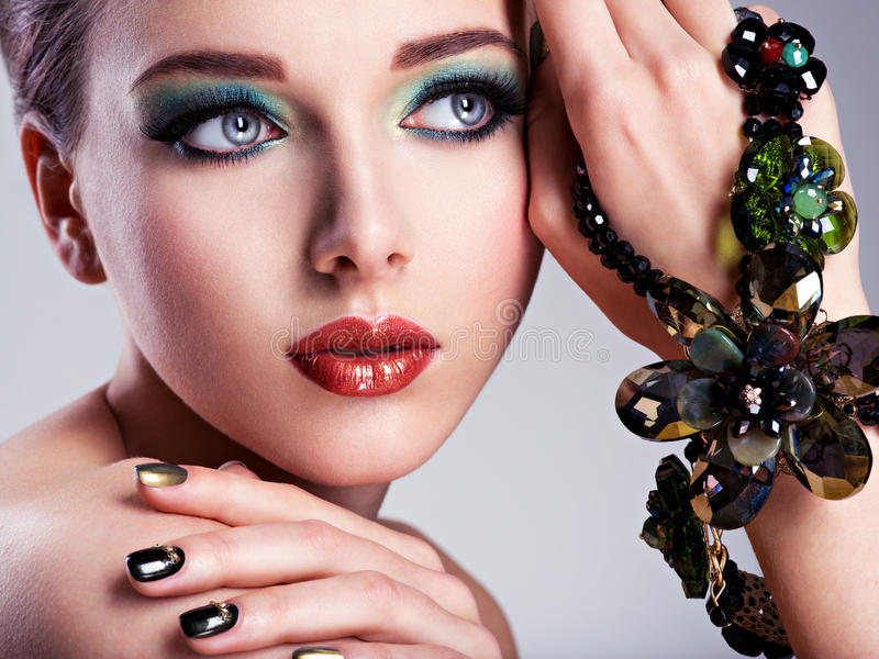 Schönheitsgesicht mit Modegrünmake-up und Schmuck auf h stockfoto