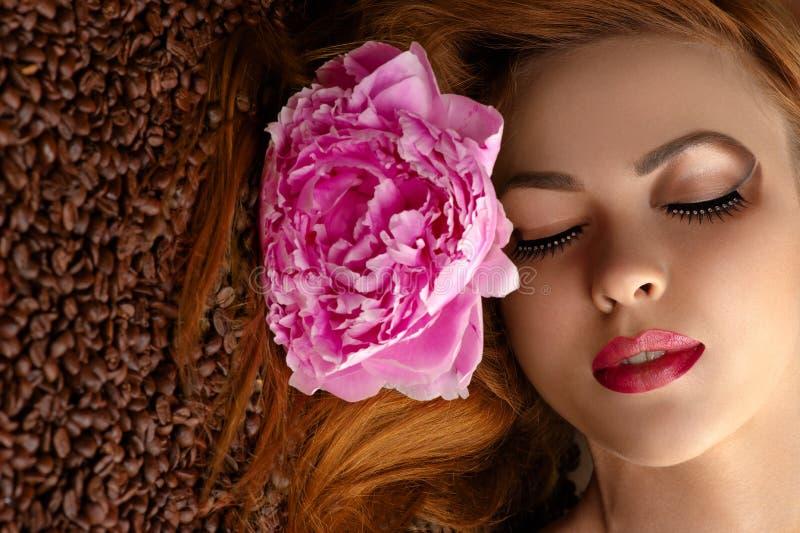 Schönheitsgesicht mit Pfingstrose auf Kaffeebohnen lizenzfreie stockbilder