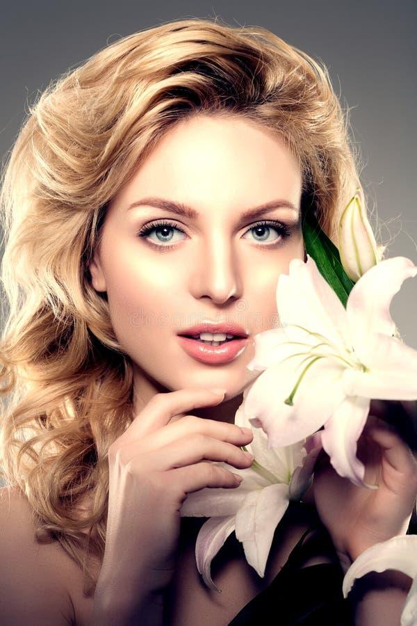 Schönheitsgesichtsfrau, Blumen, Lilie Gesundes Modell des Mädchens in Badekurort salo lizenzfreie stockfotos