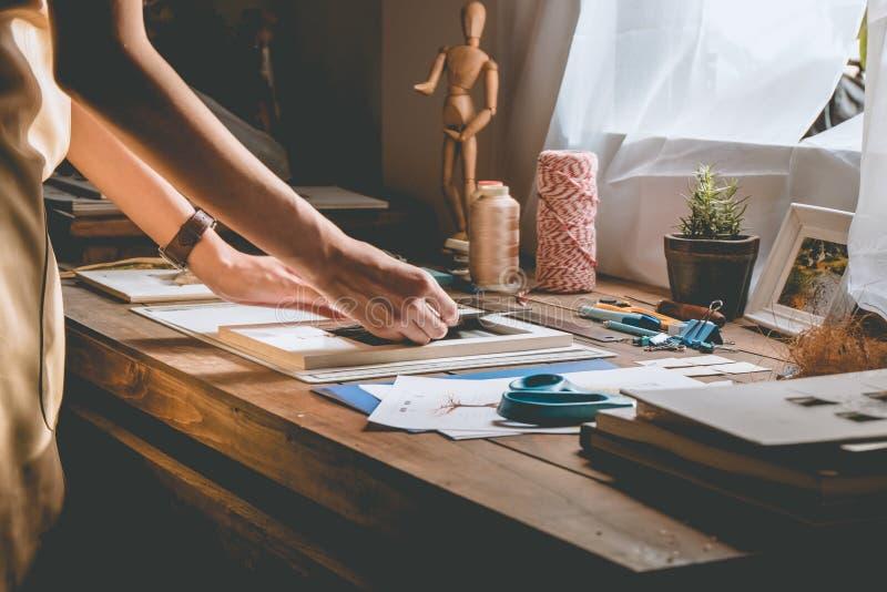 Schönheitshand, die Buch an der Tischplatte mit Briefpapier in Handarbeit macht lizenzfreies stockbild