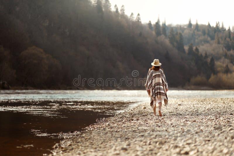 Schönheitshippie, der auf Flussstrand in den Bergen, in tragendem Hut und im Poncho, boho Reisekonzept, Raum für Text geht lizenzfreies stockbild