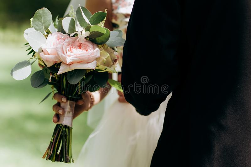 Schönheitshochzeitsblumenstrauß in Braut ` s Händen Braut hält einen leichten Blumenstrauß lizenzfreie stockfotografie