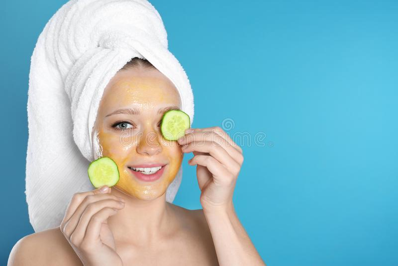 Schönheitsholding-Gurkenscheiben nahe ihrem Gesicht mit natürlicher Maske gegen Farbhintergrund stockfotografie