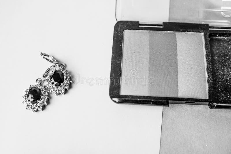 Schönheitskasten, ein Satz Kosmetik, pulverisieren und erröten mit Ohrringen für Make-up auf einem Schwarzweiss-Hintergrund Flach lizenzfreies stockbild