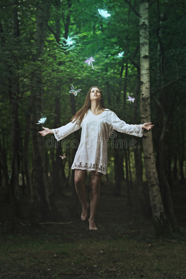 Schönheitslevitation in einem dunklen Wald stockfotografie