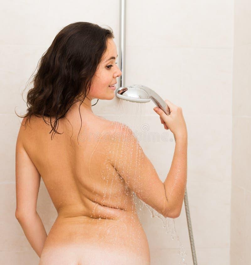 Schönheitsmädchen, das mit Dusche sich wäscht stockfoto