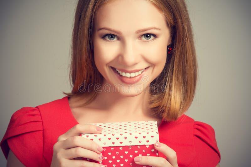 Schönheitsmädchen im roten Kleid mit Geschenkbox zum Geburtstag oder zum Valentinstag lizenzfreies stockfoto