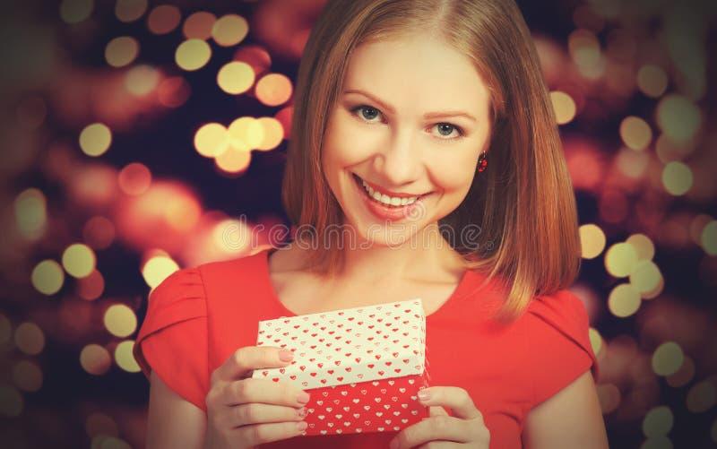 Schönheitsmädchen im roten Kleid mit Geschenkbox zum Weihnachten oder zum Valentinstag stockfoto