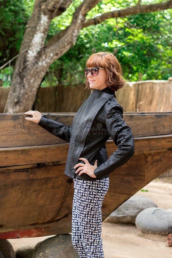 Schönheitsmädchen im stilvollem snakeskin Pythonschlangenmantel und -gläsern Art und Weiseblick Asien, Bali, Indonesien lizenzfreies stockfoto