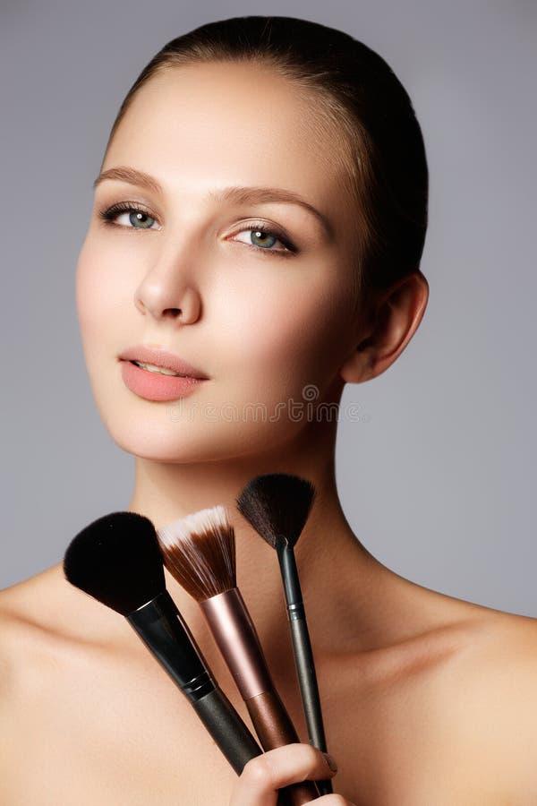 Schönheitsmädchen mit Make-upbürsten Natürlich machen Sie Brunette Wo wieder gut stockfotografie