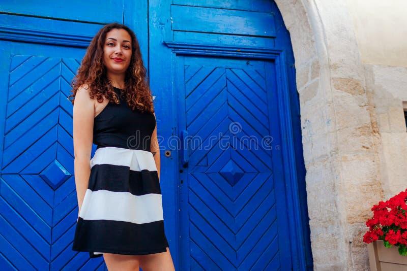 Schönheitsmode-Jungemodell Porträt im Freien des jugendlich Mädchens lächelnd gegen blaue Tür durch Café lizenzfreie stockbilder