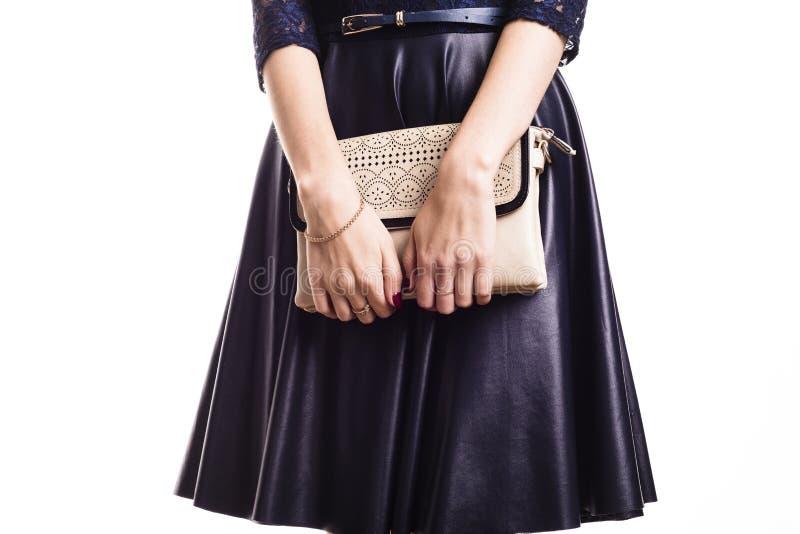Schönheitsmodell in einem Lederrock hält eine Handtasche stockbilder