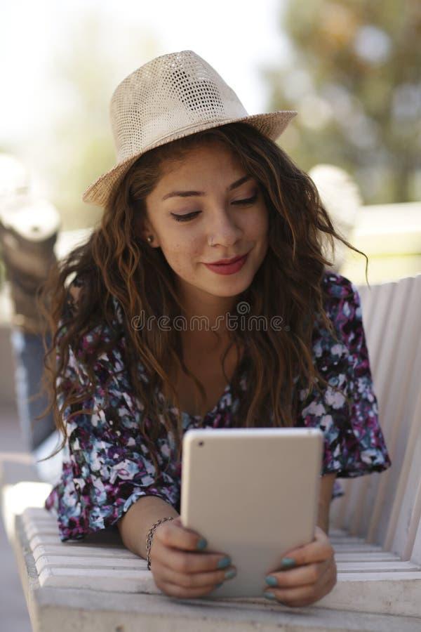 Schönheitsmodell mit Hut und mit Tablette in einem Park stockfoto