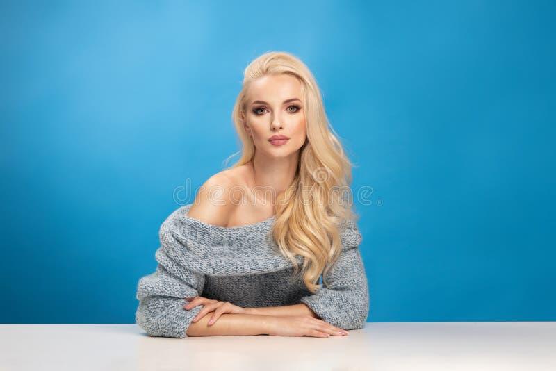 Schönheitsmodeporträt der Frau auf blauem Hintergrund stockbild