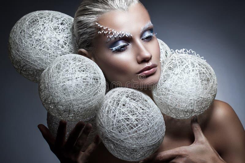 Schönheitsmodeporträt einer Schönheit mit kreativem Make-up auf ihrem Gesicht Weiße umsponnene Bälle um den Kopf des Modells lizenzfreie stockbilder