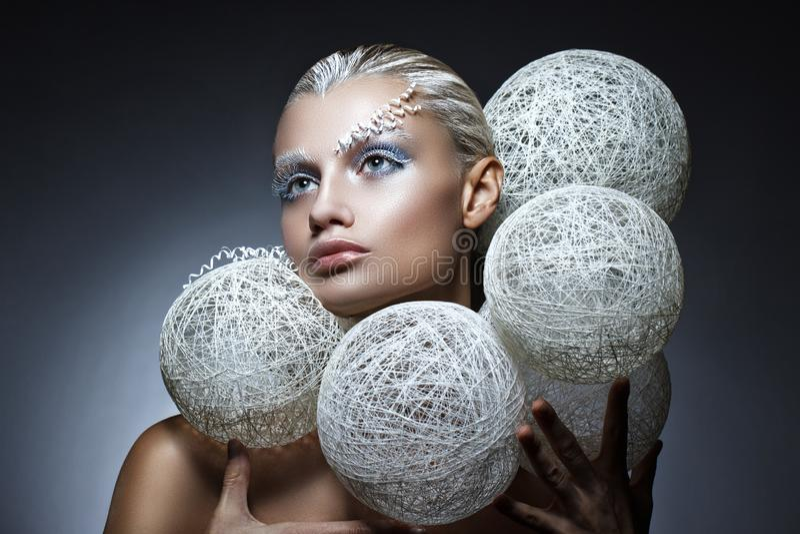 Schönheitsmodeporträt einer Schönheit mit kreativem Make-up auf ihrem Gesicht Weiße umsponnene Bälle um den Kopf des Modells lizenzfreies stockbild