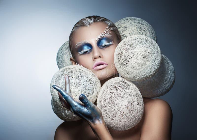Schönheitsmodeporträt einer Schönheit mit kreativem Make-up auf ihrem Gesicht Weiße umsponnene Bälle um den Kopf des Modells lizenzfreie stockfotos