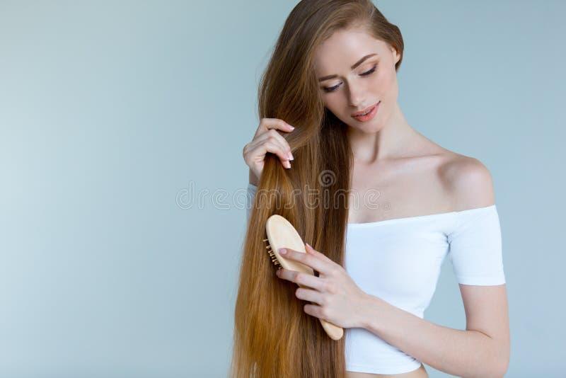 Schönheitsnahaufnahmeporträt der schönen jungen Frau mit dem langen braunen Haar auf weißem Hintergrund Haarpflegekonzept stockfoto