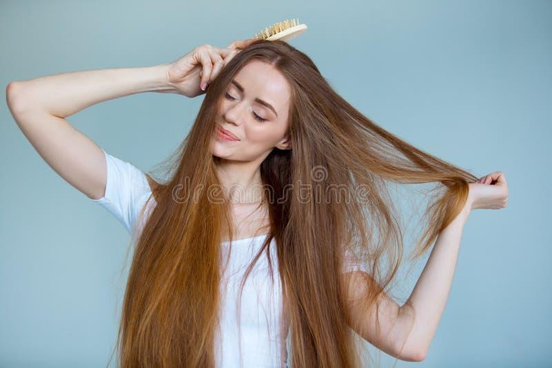 Schönheitsnahaufnahmeporträt der schönen jungen Frau mit dem langen braunen Haar auf weißem Hintergrund Haarpflegekonzept stockfotos