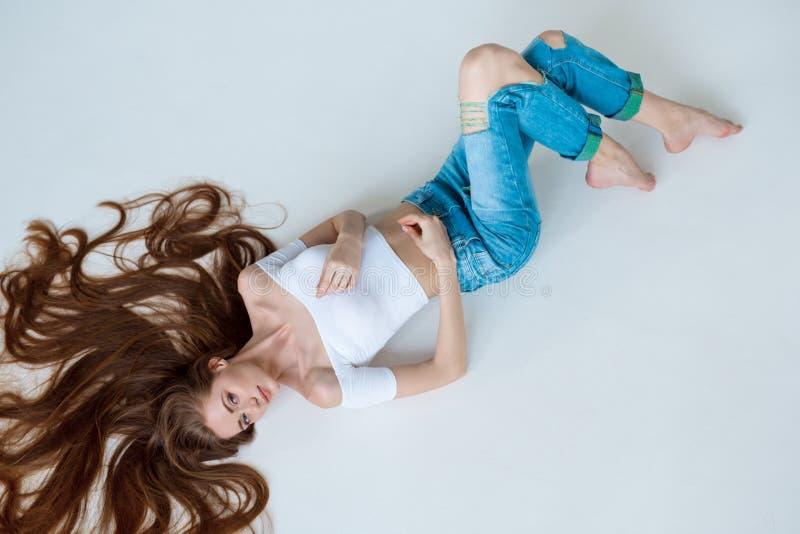 Schönheitsnahaufnahmeporträt des schönen weiblichen Gesichtes mit dem langen braunen Haar, das auf dem Weiß niederlegt Haarpflege stockfoto