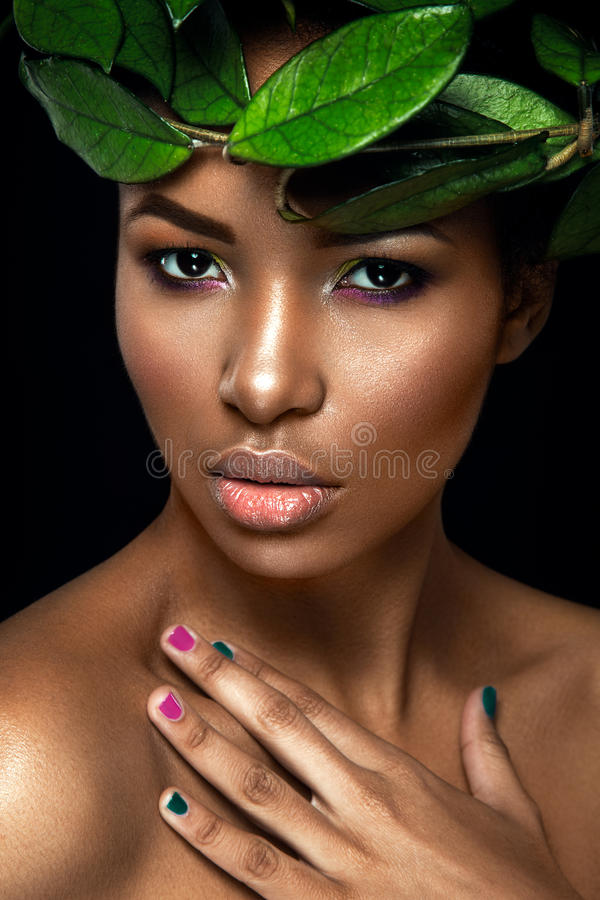 Schönheitsporträt auf schwarzem Hintergrund Junges Afromädchen, das mit grünen Blättern aufwirft Herrlich bilden Sie stockbilder