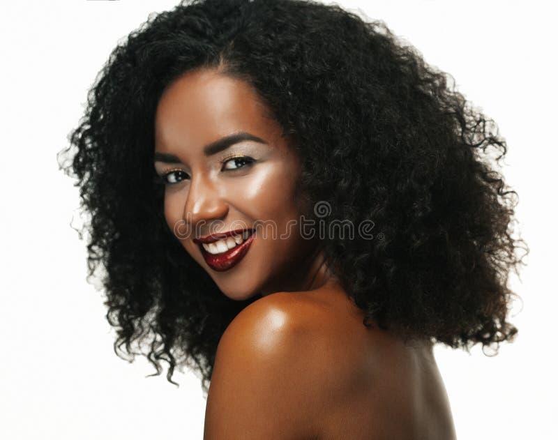 Schönheitsporträt der attraktiven Afroamerikanerfrau mit großem Afro- und Zaubermake-up stockfoto