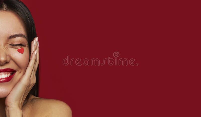Schönheitsporträt der brunette glücklichen Frau mit Herzen auf ihrem Gesicht Valentinstagporträt der attraktiven lächelnden Frau, lizenzfreie stockfotos