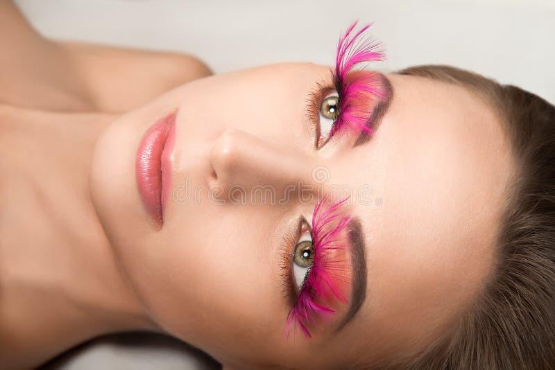 Schönheitsporträt der Frau mit rosa Feder peitscht lizenzfreie stockfotos