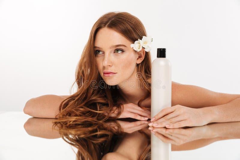 Schönheitsporträt der Geheimnisingwerfrau mit Blume im Haar stockfoto