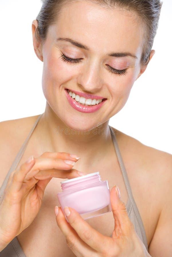 Schönheitsporträt der glücklichen jungen Frau mit Creme stockbild