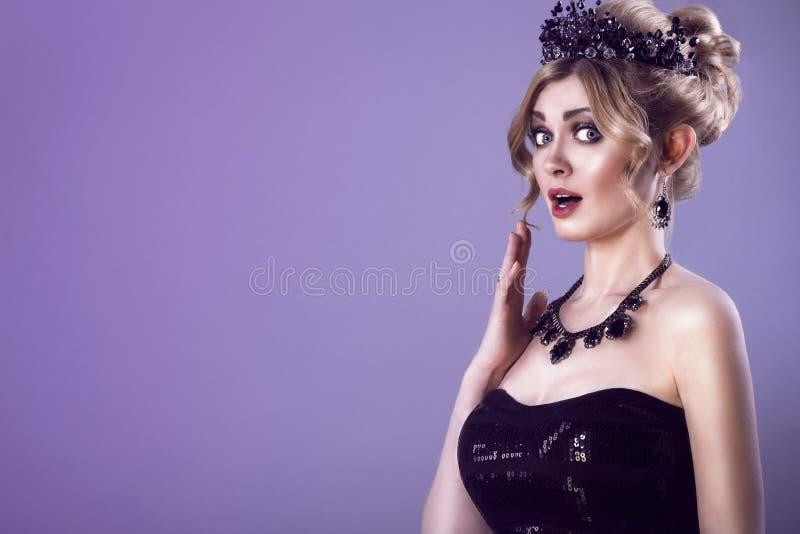 Schönheitsporträt der herrlichen extrem überraschten jungen blonden Frau mit updo Haar und schwarzer Juwelkrone auf ihrem Kopf stockbild
