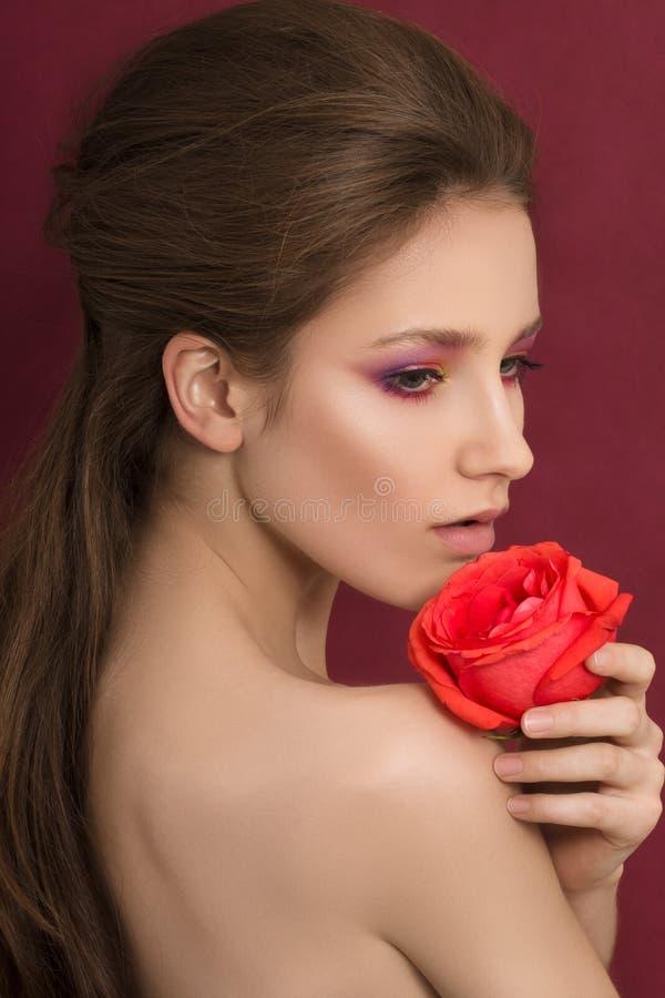 Schönheitsporträt der jungen Brunettefrau, die Rotrose hält lizenzfreie stockfotografie