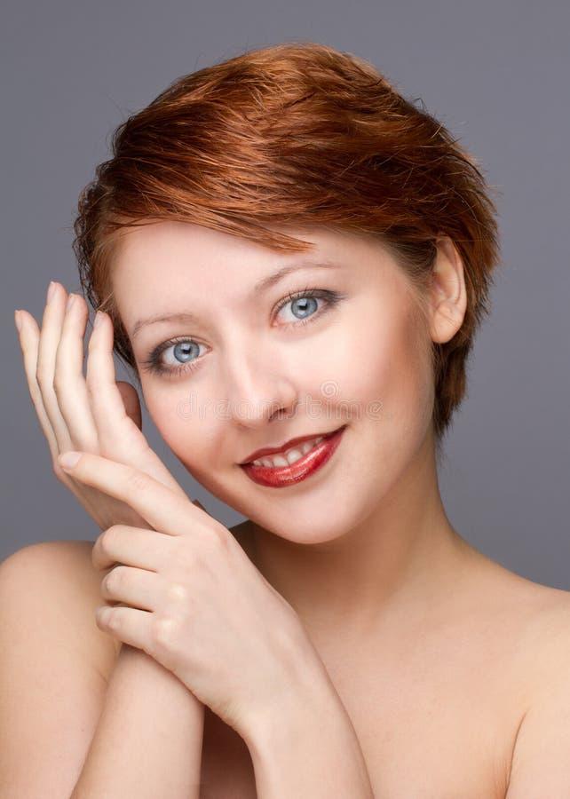 Schönheitsporträt der jungen Frau auf Grau lizenzfreie stockbilder