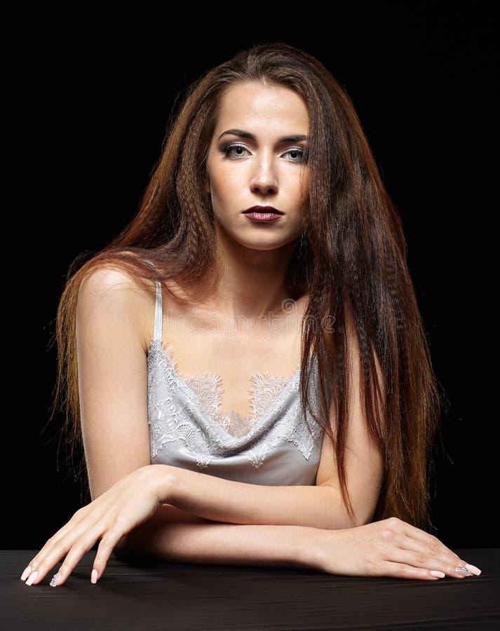 Schönheitsporträt der jungen Frau sitzen am schwarzen Tisch Brunette stockfotografie