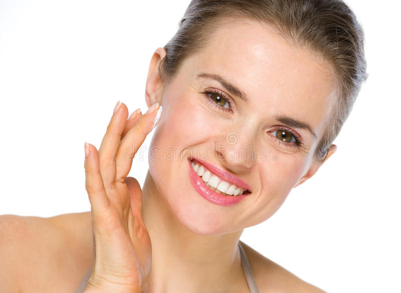 Schönheitsporträt der lächelnden Frau Creme anwendend lizenzfreie stockbilder