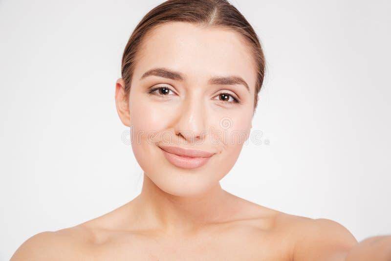 Schönheitsporträt der reizend lächelnden jungen Frau, die selfie nimmt stockfoto
