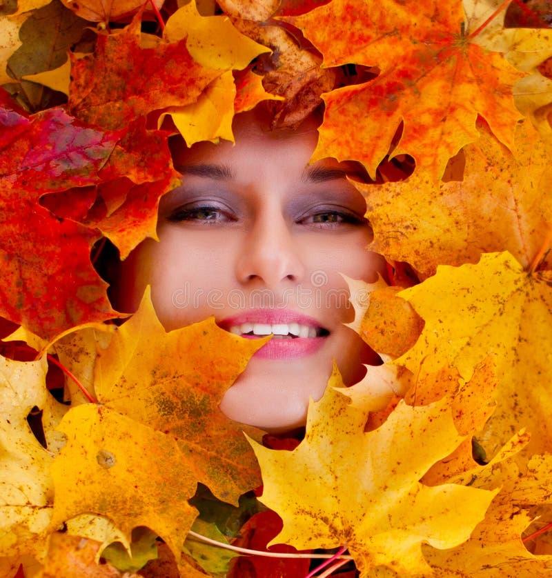 Schönheitsporträt des schönen weiblichen Gesichtes mit Herbstlaub lizenzfreie stockfotografie