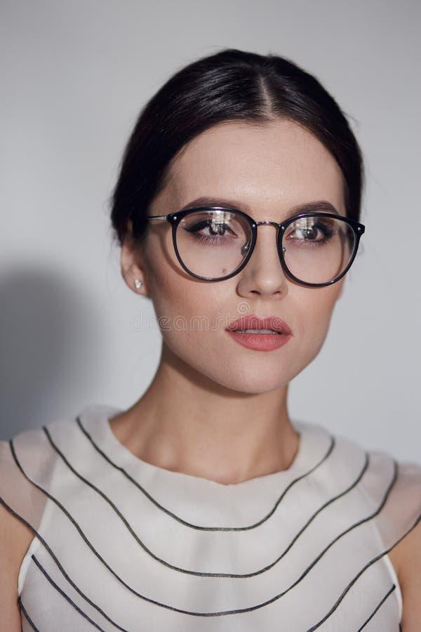 Schönheitsporträt einer jungen eleganten Frau in der Brille, lokalisiert auf einem weißen Hintergrund Vertikale Ansicht lizenzfreies stockbild