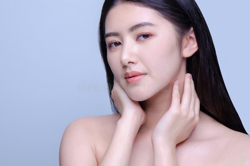 Schönheitsporträt einer jungen Schönheit mit der Hand auf ihrer Halsschulter lokalisiert auf dem grauen Hintergrund, der Kamera,  lizenzfreie stockbilder
